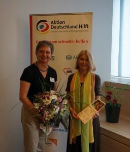 Geschäftsführerin Manuela Roßbach gratuliert Susanne Brandt (von links)c Aktion Deutschland hilft